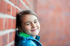 Portrait of   little cute girl next to Brick Wall Royalty Free Stock Images