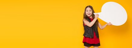 Little brunette girl with speech bubble. Portrait of little cute girl in red shirt holding blank white speech bubble with empty space for text isolated on orange Stock Image