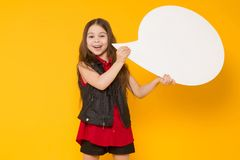 Little brunette girl with speech bubble. Portrait of little cute girl in red shirt holding blank white speech bubble with empty space for text isolated on orange Royalty Free Stock Images
