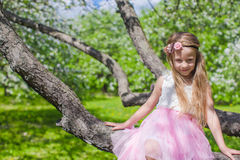 Portrait of little cute girl sitting on blossoming Royalty Free Stock Photography