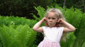 Portrait of little cute girl with sweet cherry berries as earrings on ears. Gimbal stabilizer motion movement shot stock video footage