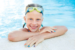 Portrait of little cute girl in the swimming pool. Sunny summer day Stock Photo