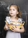 Portrait of little cute girl writing on the blackboard. With chalk Royalty Free Stock Photo