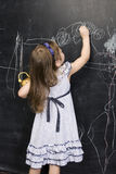 Portrait of little cute girl writing on the blackboard. With chalk Stock Image