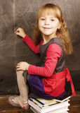 Portrait of little cute girl writing on the blackboard. In classroom Royalty Free Stock Image