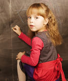 Portrait of little cute girl writing on the blackboard. In classroom Stock Photography