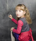 Portrait of little cute girl writing on the blackboard. Close up Royalty Free Stock Images