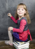 Portrait of little cute girl writing on the blackboard. Close up Royalty Free Stock Image
