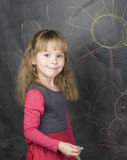 Portrait of little cute girl writing on the blackboard Royalty Free Stock Images