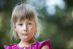 Portrait of little cute pretty young child girl with gray eyes and scattered blond hair with funny face expression on blurred gree. N outdoor sunny background royalty free stock image