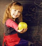 Portrait of little cute real girl writing on the blackboard. Portrait of little cute girl writing on the blackboard with green apple Stock Photo