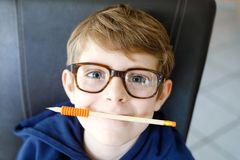 Portrait of little cute school kid boy with glasses. Beautiful happy child looking at the camera. Schoolboy making fun royalty free stock images
