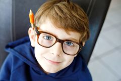 Portrait of little cute school kid boy with glasses. Beautiful happy child looking at the camera. Schoolboy making fun stock image