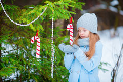 Portrait of a little cute smiling girl in a blue coat and mittens standing near the decorated Christmas tree on a frosty Stock Photos