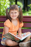 Portrait of little cute smiling girl with book. Portrait of little cute smiling girl preschooler with open book who is sitting cross-legged on the wooden bench Royalty Free Stock Image