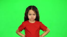Portrait of little dark girl showing emotion on green background. Portrait of little dark-haired girl in red T-shirt showing emotion punishment keying or stock footage