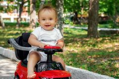 Portrait of a little driver: happy infant child with surprised face sitting barefoot on a red push car outdoor in the park stock image