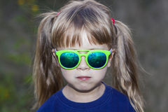 Portrait of little fashionable girl in green sunglasses outdoors. Portrait of little fashionable girl green sunglasses outdoors Royalty Free Stock Photo