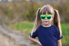 Portrait of little fashionable girl in green sunglasses outdoors Stock Photo