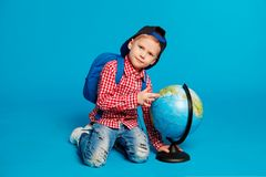 Portrait of little funny boy with backpack and cap. Showing place on the globe, map. Concept travel, education. On the blue background Royalty Free Stock Photography