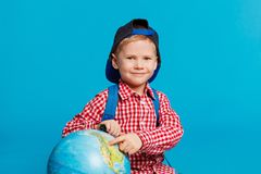 Portrait of little funny boy with backpack and cap. Showing place on the globe, map. Concept travel, education. On the blue background Stock Photos