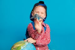 Portrait of little funny boy with backpack,cap and toy paper plane. Showing place on the globe, map. Concept travel. Education. On the blue background Stock Images