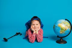 Portrait of little funny boy with backpack, globe and action camera. Concept travel, education. On the blue background Stock Images