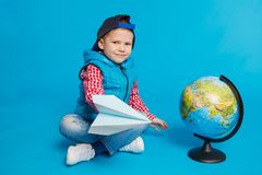 Portrait of little funny boy with cap and toy paper plane. Showing place on the globe, map. Concept travel, education. On the blue background Royalty Free Stock Photography