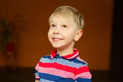Portrait of little boy over yellow background looking above Royalty Free Stock Images