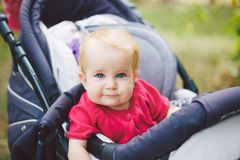 Portrait of a little funny child girl blond with blue eyes sitting in a baby stroller in the summer for greens. Trinasport for a c. Hild and transportation of Stock Photo