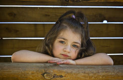 Portrait of little girl. A cute  thoughtful  little girl on the wooden background with his head on his hands Stock Photos
