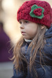 Portrait of little girl. Portrait of serious little girl in red knitted hat Stock Photos