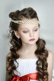 Portrait of little girl. Beautiful girl in a white dress with a string of pearls in the hair royalty free stock photos