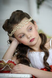 Portrait of little girl. Beautiful girl in a white dress with a string of pearls in the hair stock images