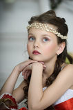 Portrait of little girl. Beautiful girl in a white dress with a string of pearls in the hair stock photo