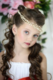 Portrait of little girl. Beautiful girl in a white dress with a string of pearls in the hair royalty free stock image