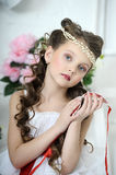 Portrait of little girl. Beautiful girl in a white dress with a string of pearls in the hair stock photography