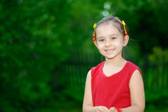 Portrait of the little girl. The girl of preschool age against a green lawn with a fence Royalty Free Stock Images