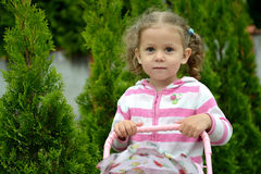 Portrait of the little girl against the background of coniferous. Plants Royalty Free Stock Photo
