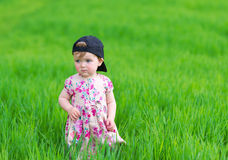 Portrait of the little girl against green grass. Stock Photography