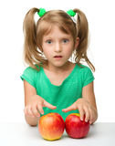 Portrait of a little girl with apple. Portrait of a cute little girl with two red apples, isolated over white stock photo