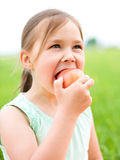 Portrait of a little girl with apple Stock Image