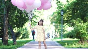 Portrait of little girl with balloons in her hands. carefree and happy child outdoors. Children run through the Park with a huge bunch of colorful balloons. two stock video footage