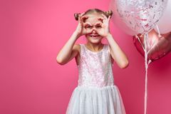 Portrait of a little girl with balls, on a pink background in a photo Studio, close-up stock image