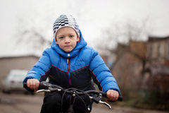 Portrait of a little girl on a bicycle in the cold autumn Stock Photo