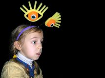 Portrait of a little girl with big eyes on a black background. Surprised little girl wearing headband with big toy eyes. Girl`s eyes widened and mouth opened in Stock Photography