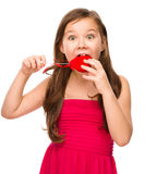 Portrait of a little girl biting red heart Royalty Free Stock Photos