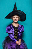 Portrait of little girl in black hat and witch clothing. Halloween. Fairy. Tale. Studio portrait on blue background Stock Image