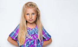 Portrait of a little girl with blond long hair. Little girl is standing on a white background. Little girl dressed in plaid shirt Stock Photos