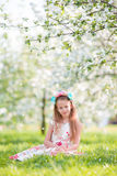 Portrait of little girl in blooming apple tree garden outdoors Stock Photo